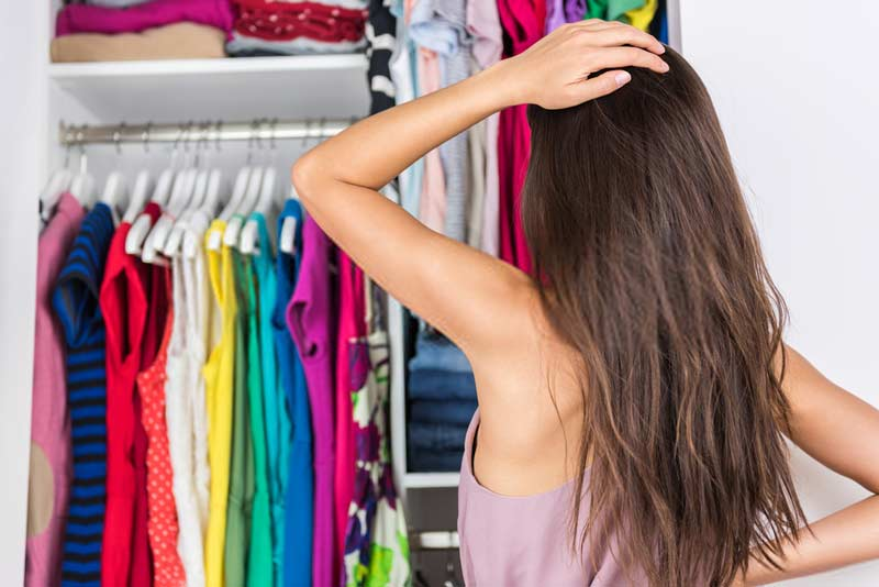 Home closet indecision woman choosing her fashion outfit on clothing rack
