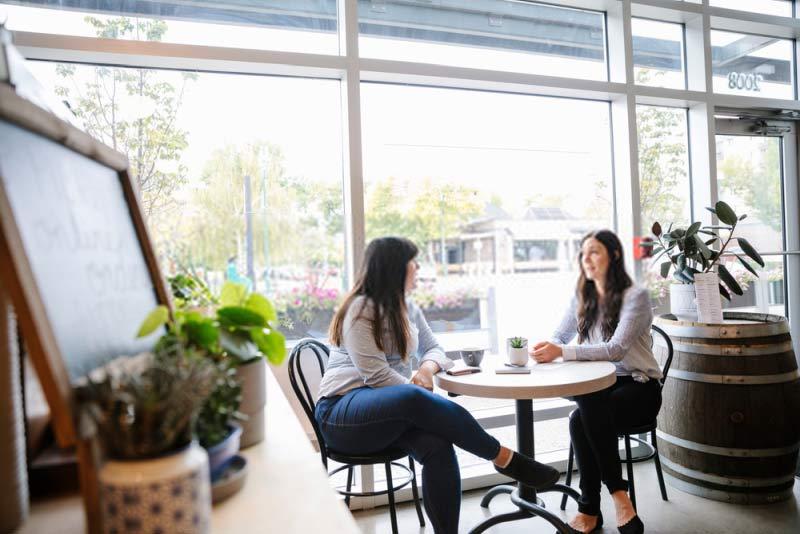 Due donne sedute a parlare al caffè